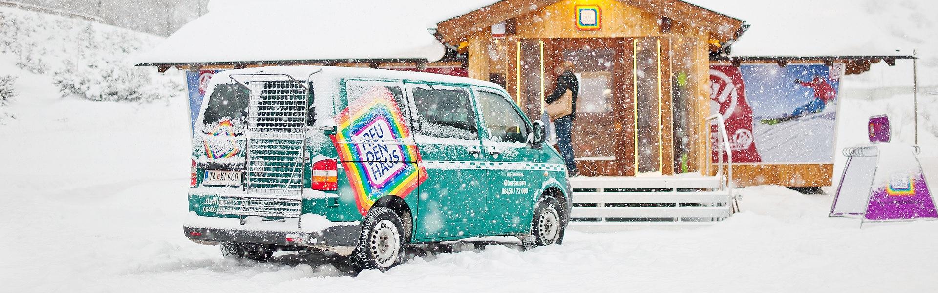 Auto vor Haus in Schnee während es schneit